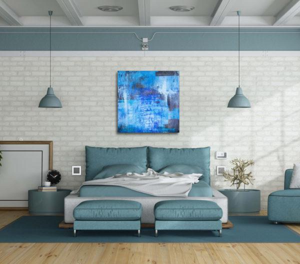 Imagen de un cuadro abstracto con tonos azules, expuesto sobre la cabecera de la cama en una habitación