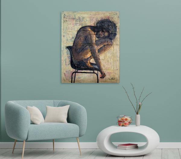 Imagen del cuadro de una mujer sentada, expuesto junto a una butaca de una salita