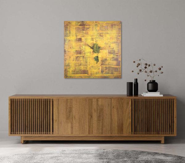 Cuadro abstracto expuesto sobre una cómoda de un salón